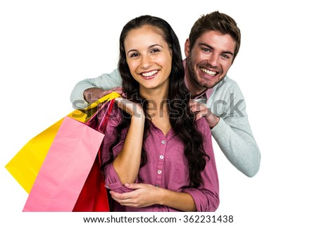 Portrait of cheerful couple holding colorful shopping bags on white background - stock photo