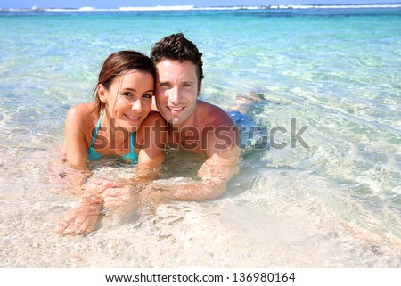 Portrait of cheerful couple in Caribbean sea - stock photo