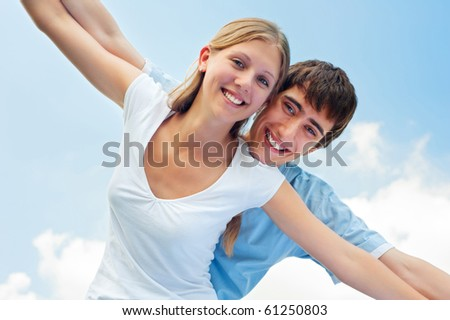 portrait of cheerful couple in love over blue sky