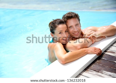 Portrait of cheerful couple in swimming-pool - stock photo