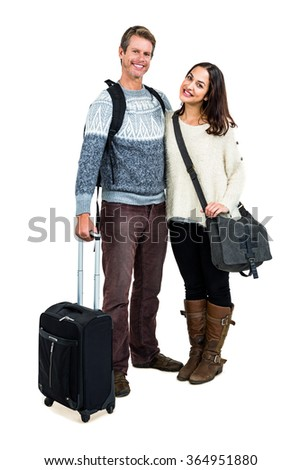 Portrait of cheerful couple in warm clothing with luggage against white background - stock photo