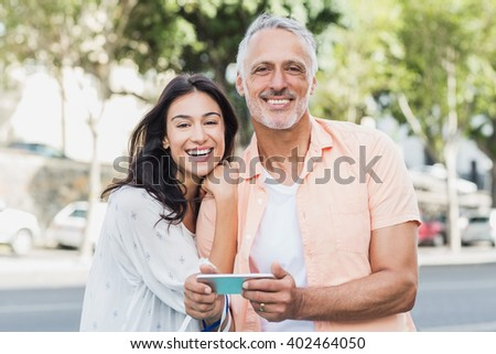 Portrait of cheerful couple using phone in city - stock photo