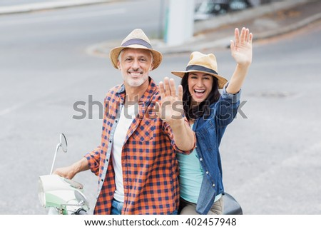 Portrait of cheerful couple waving hands while riding moped in city - stock photo