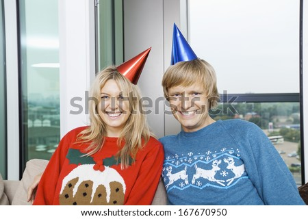 Portrait of cheerful couple wearing Christmas sweaters and party hats in living room at home - stock photo
