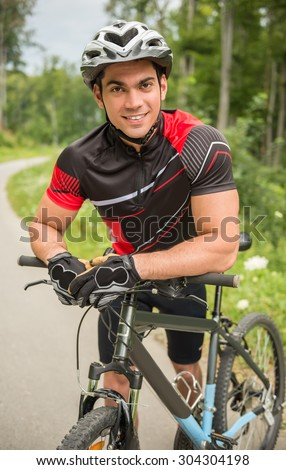 Portrait of cheerful cyclist leaning on his bike on the forest road.