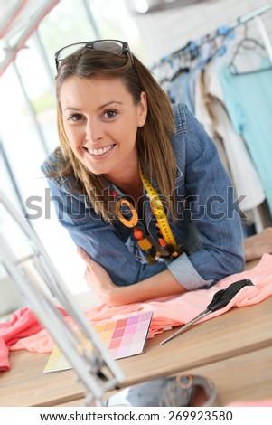 Portrait of cheerful dressmaker in designing studio - stock photo