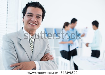 Portrait of cheerful experienced businessman and his team in the background - stock photo