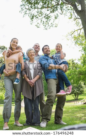 Portrait of cheerful extended family standing at the park - stock photo