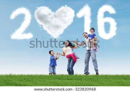 Portrait of cheerful family celebrate new year on the meadow and jumping together with cloud shaped numbers 2016