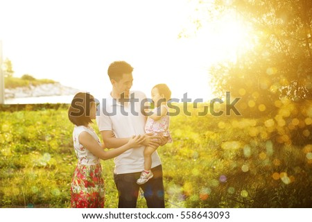 Portrait of cheerful family enjoying outdoor activity together, walking on garden park in beautiful sunset during holiday vacations.
