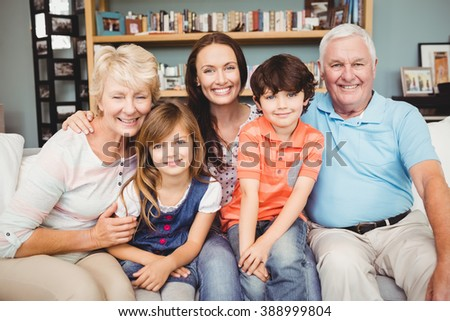 Portrait of cheerful family sitting on sofa at home - stock photo