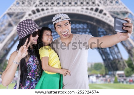 Portrait of cheerful family taking selfie photo with camera phone at the Eiffel Tower in Paris - stock photo