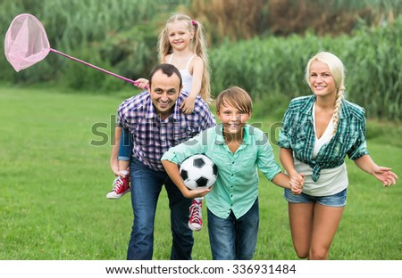 Portrait of cheerful family with kids enjoying vacation in village