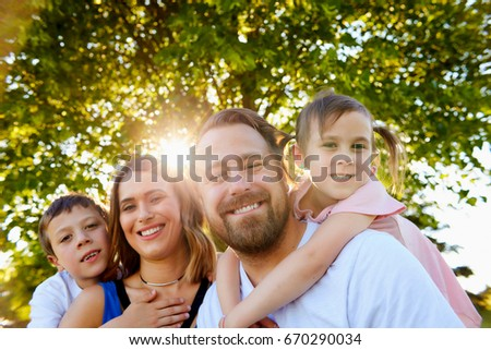 Portrait of cheerful family with two little children, embracing, looking at camera and smiling in summer