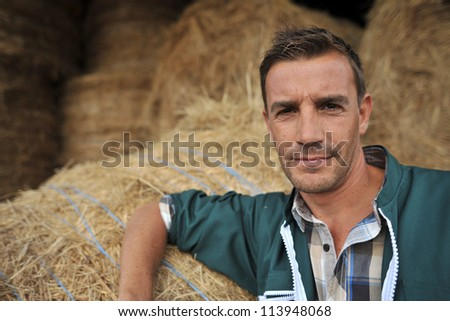Portrait of cheerful farmer standing in front of hay rolls - stock photo