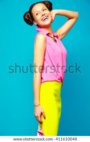 portrait of cheerful fashion hipster girl in casual colorful vivid hipster blue and pink summer clothes on blue background with toy in hands - stock photo