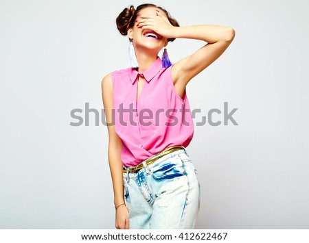 portrait of cheerful fashion hipster girl in casual colorful vivid hipster blue and pink summer clothes jeans on gray background covering her eyes with hands