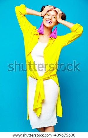 portrait of cheerful fashion hipster girl in casual colorful vivid hipster yellow summer clothes on blue background