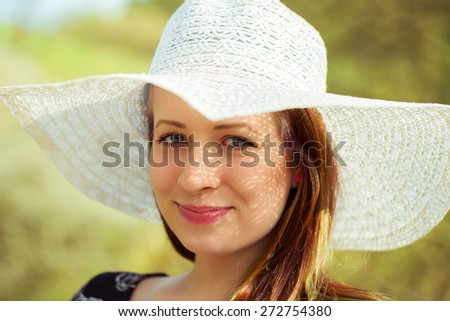 Portrait of cheerful fashionable woman in stylish hat and frock posing outdoor. Happy brunette girl with long hair in warm spring day - stock photo