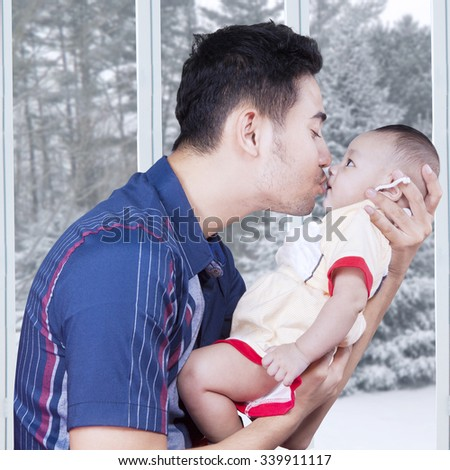 Portrait of cheerful father holding his male baby at home and kissing the baby, shot with winter background on the window