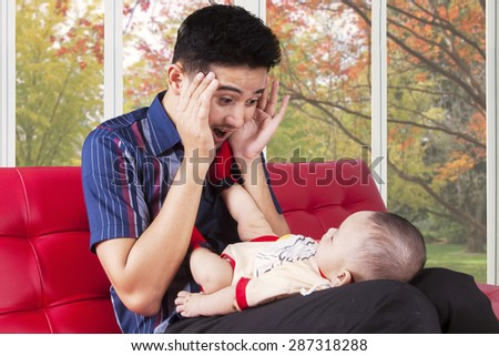 Portrait of cheerful father sitting on the sofa while playing peekaboo with his baby at home - stock photo