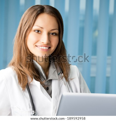 Portrait of cheerful female doctor working with laptop at office