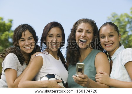Portrait of cheerful female friends with mobilephone and soccer ball at park - stock photo