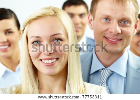 Portrait of cheerful female looking at camera with several employees behind