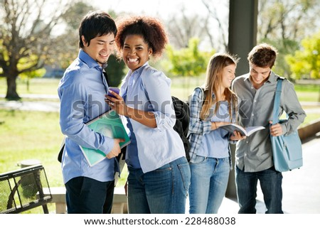Portrait of cheerful female student showing cellphone to friend while classmates standing in background at college campus - stock photo