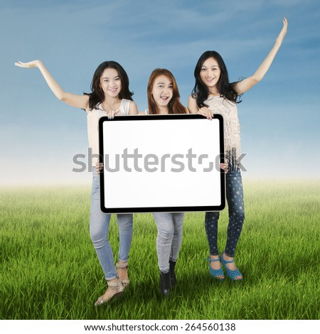 Portrait of cheerful female students standing on the meadow while holding empty board - stock photo