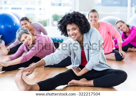 Portrait of cheerful fit women touching toes in fitness studio - stock photo