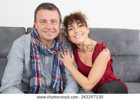 Portrait of cheerful forty years old couple sitting on sofa in modern white apartment - stock photo