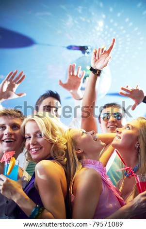 Portrait of cheerful friends dancing and having fun at party in club