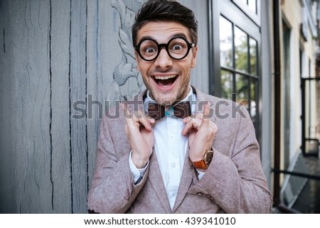 Portrait of cheerful funny young man in round glasses and wooden bowtie standing outdoors - stock photo
