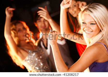Portrait of cheerful girl dancing at party with her friends behind