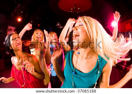 Portrait of cheerful girl dancing at party with her friends on background - stock photo