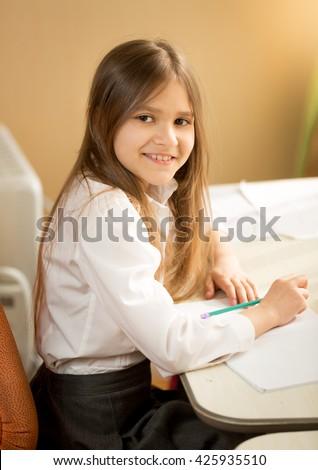 Portrait of cheerful girl doing homework behind desk - stock photo