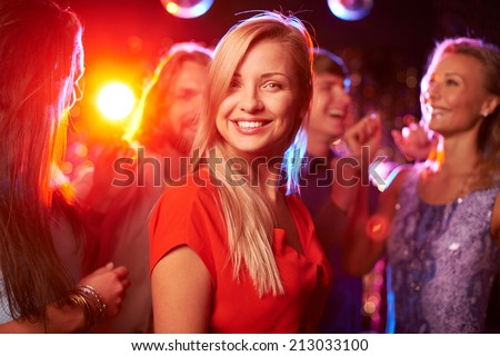 Portrait of cheerful girl looking at camera at party on background of her friends - stock photo