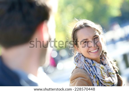 Portrait of cheerful girl pulling boyfriend by arm in Central Park - stock photo