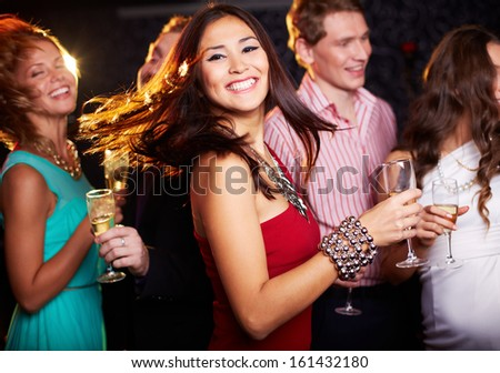 Portrait of cheerful girl with champagne flute dancing at party while smiling at camera