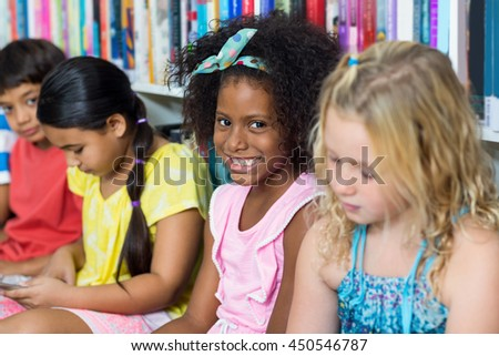 Portrait of cheerful girl with classmates in library