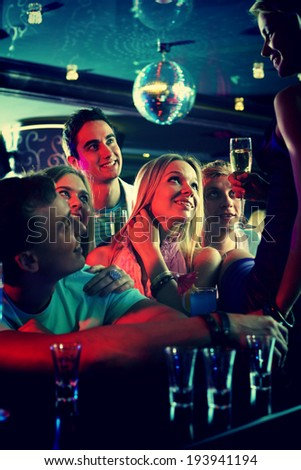 Portrait of cheerful girls and guys with cocktails looking at their friend in the bar - stock photo