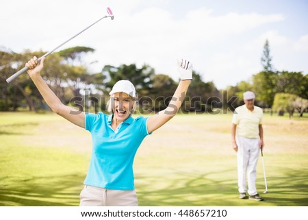 Portrait of cheerful golfer woman with arms raised while standing on field - stock photo