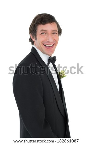 Portrait of cheerful groom in tuxedo over white background