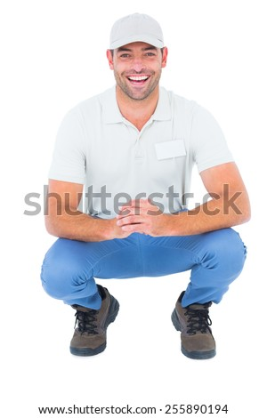 Portrait of cheerful handyman crouching on white background - stock photo