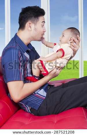 Portrait of cheerful little baby playing with his father on the sofa at home - stock photo