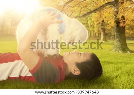 Portrait of cheerful little boy lying on the grass while playing with his dog at the autumn park - stock photo