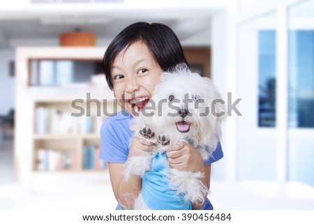 Portrait of cheerful little girl holding a maltese dog at home while playing together - stock photo