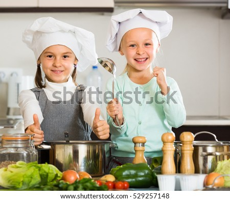 Portrait of cheerful little sisters in caps learning how to cook