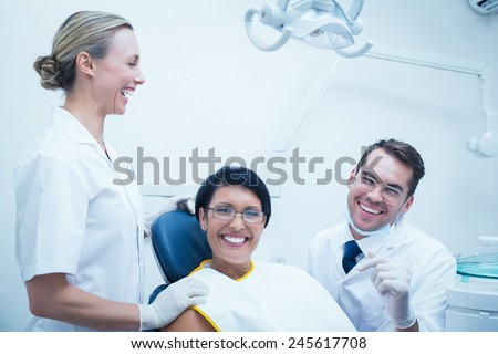 Portrait of cheerful male dentist and assistant with female patient in the dentists chair - stock photo